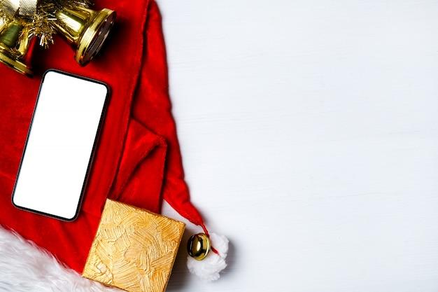 Smartphone, geschenk und glocken auf santa claus hut