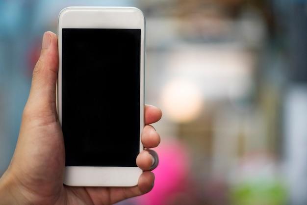Smartphone-hand - bemannen sie die hand, die den weißen smartphone mit schwarzem schirm hält - unter verwendung des handyfreien raumes