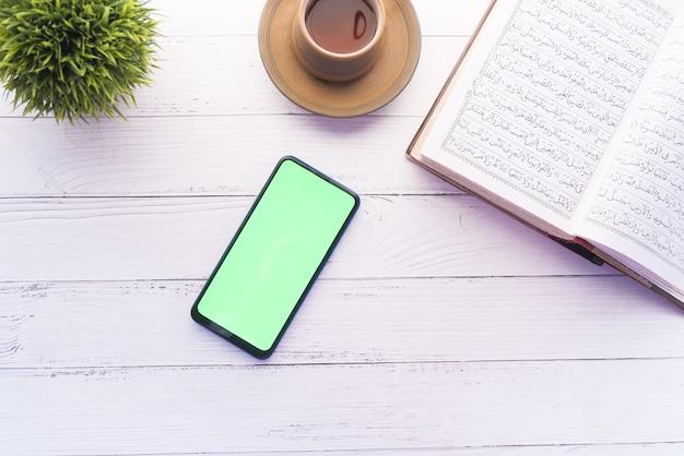 Smartphone, heiliges buch koran und rosenkranz auf dem tisch,