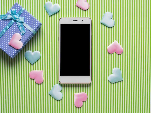 Smartphone, herzen und pastellgeschenkbox