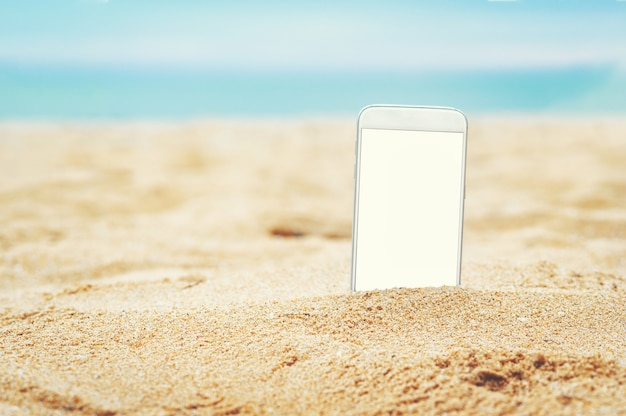 Smartphone im sand am strand im sommer