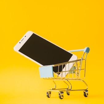 Smartphone im spielzeug supermarkt warenkorb