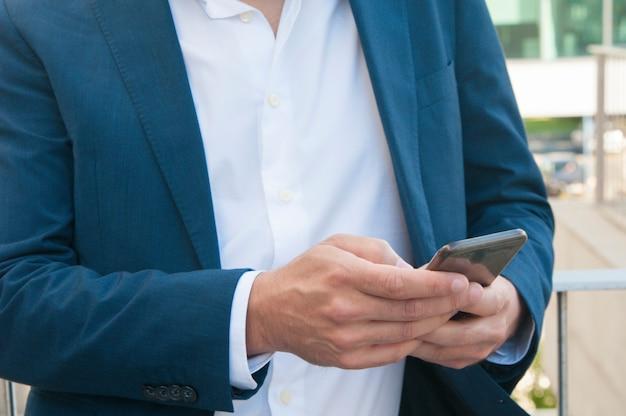 Smartphone in den geschäftsmannhänden