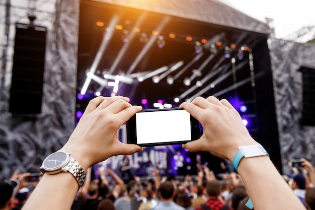 Smartphone in den händen auf musikshow. leerer bildschirm