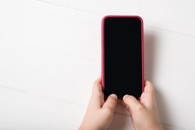 Smartphone in den händen der kinder auf einem hellen hintergrund
