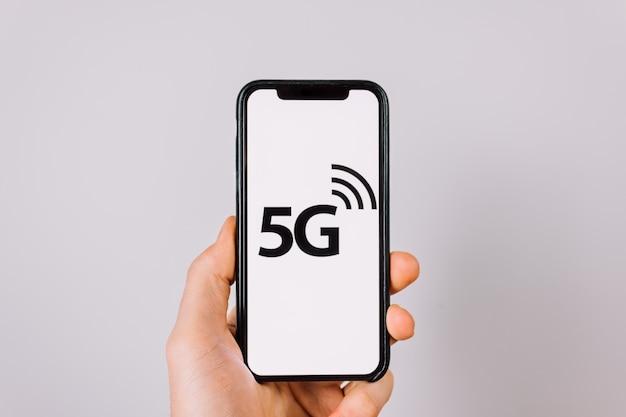 Smartphone in der hand mit dem logo von 5g internet-netzwerken auf dem bildschirm