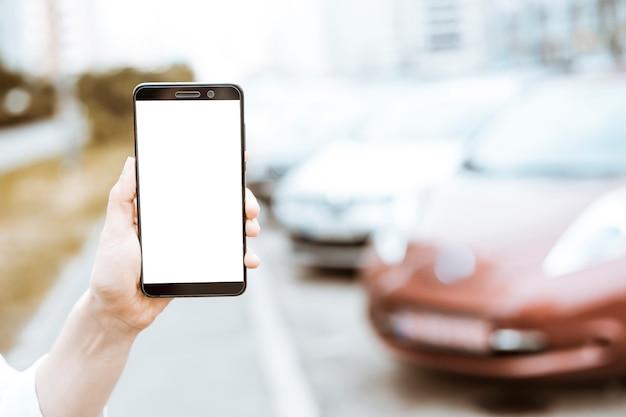Smartphone in der hand mit einem weißen bildschirm auf dem hintergrund von geparkten autos.