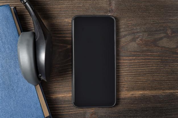 Smartphone in der nähe, um auf hölzernem hintergrund zu buchen. speicherplatz kopieren, draufsicht