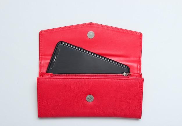 Smartphone in einer roten lederbrieftasche auf weiß. draufsicht