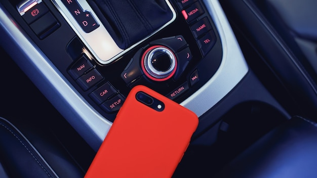 Smartphone in roter hülle mit dual-kamera im innenraum eines modernen luxusautos