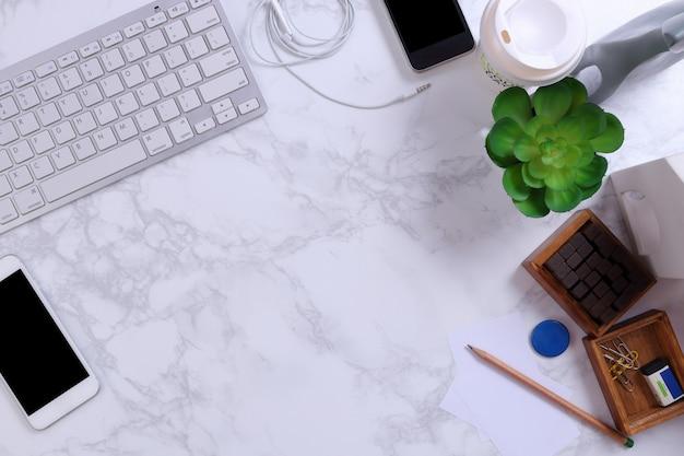 Smartphone, kayboard und bürozubehöre auf marmorhintergrund