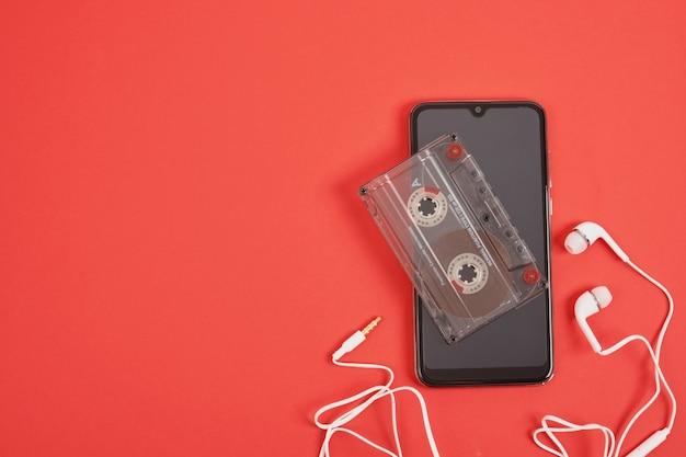Smartphone-kopfhörer und audiokassette auf rotem hintergrund, speicherkonzept, moderne technologien und technologien der vergangenheit