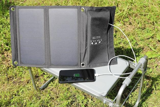 Smartphone lädt vom solarladegerät in der natur