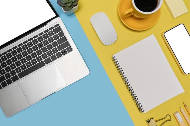 Smartphone, laptop-computer und kaffeetasse auf blauem und gelbem hintergrund mit zwei tönen.