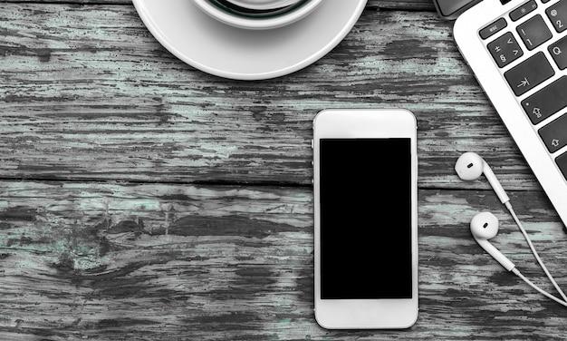 Smartphone, laptop, tastatur und kaffeetasse auf dem holzhintergrund
