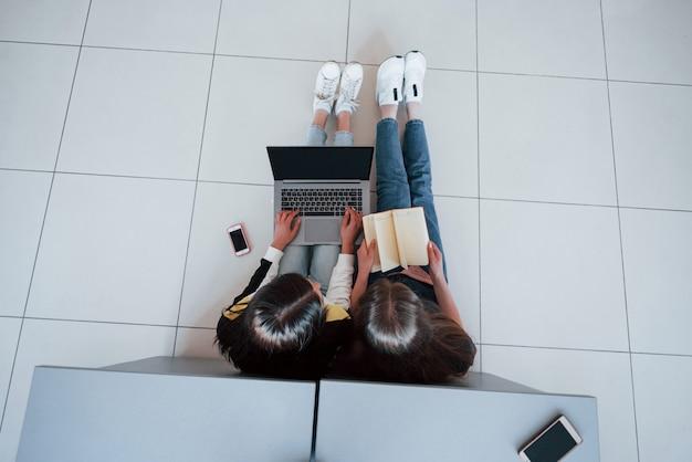 Smartphone, laptop und buch. draufsicht der jungen leute in der freizeitkleidung, die im modernen büro arbeiten