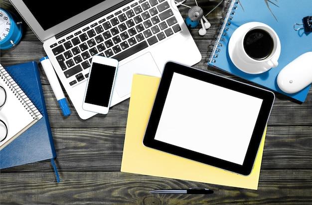 Smartphone, laptop und tablet-pc mit kaffee im hintergrund