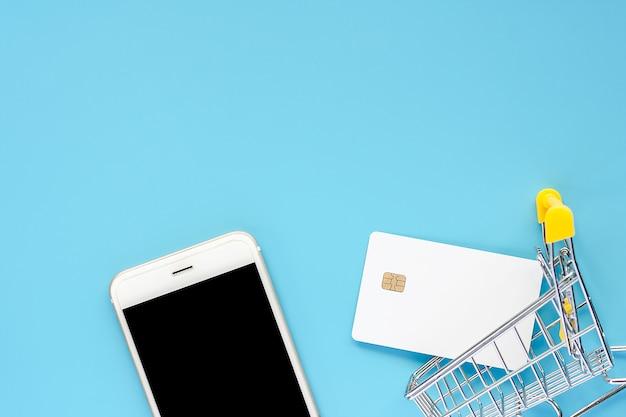 Smartphone, leere weiße kreditkarte und minieinkaufswagen oder laufkatze auf blauem hintergrund