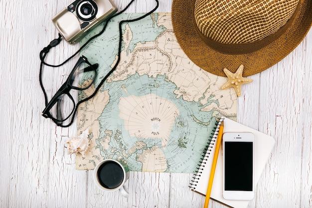 Smartphone liegt auf einem notebook vor einer tasse kaffee auf der karte, hut, kamera und brille um ihn herum