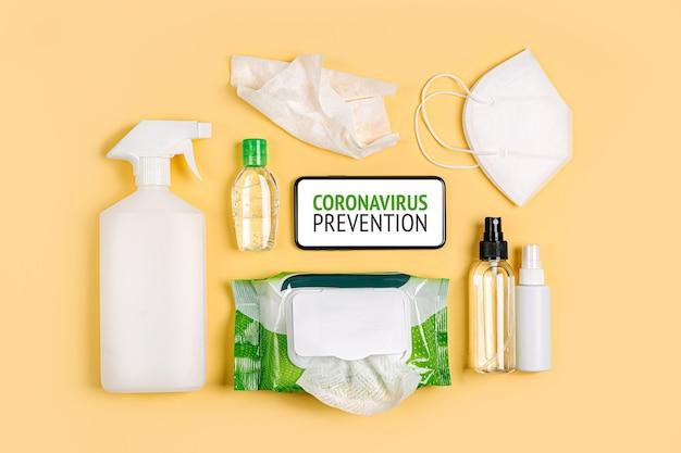 Smartphone, medizinische masken, antibakterielle feuchttücher und handdesinfektionsmittel auf gelbem hintergrund. persönliches hygieneprodukt zum schutz vor viren, grippe, coronavirus, covid-19