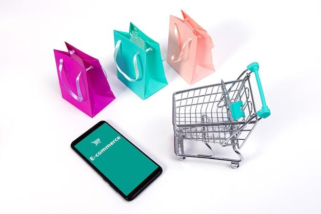 Smartphone, mini-einkaufswagen mit kreditkarten und bunten papiertüten isoliert auf weiß, e-commerce