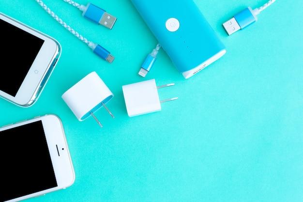 Smartphone mit adapter und usb-ladekabeln in der draufsicht