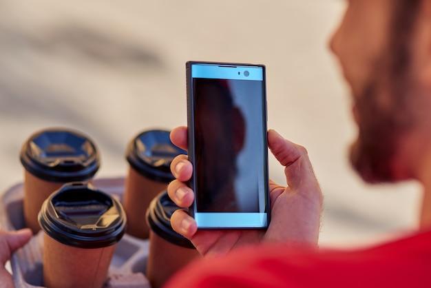 Smartphone mit aktivem bildschirm in der hand des kuriers neben kaffeetassen im freien. konzept der essenslieferung