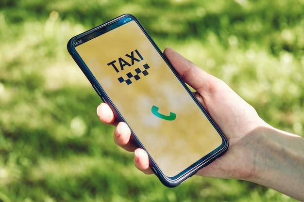 Smartphone mit app zum anrufen eines taxis in der hand.
