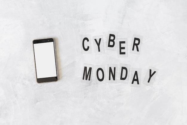 Smartphone mit cyber montag inschrift auf dem tisch