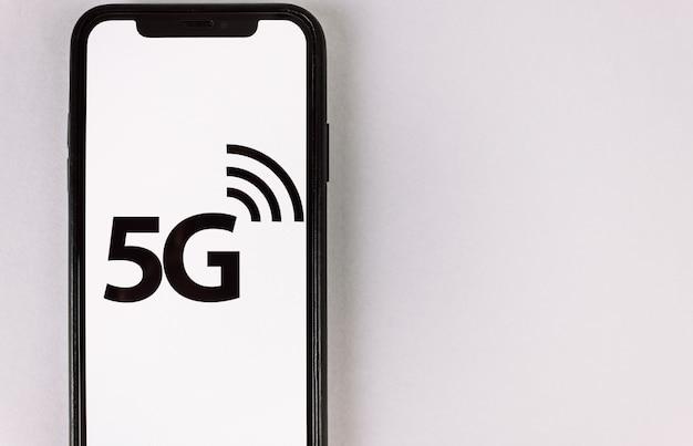 Smartphone mit dem logo von 5g internet-netzwerken auf dem bildschirm. speicherplatz kopieren