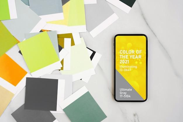 Smartphone mit den farben des jahres 2021 - ultimate grey und illuminating and fashion farbfelder. farbtrendpalette.