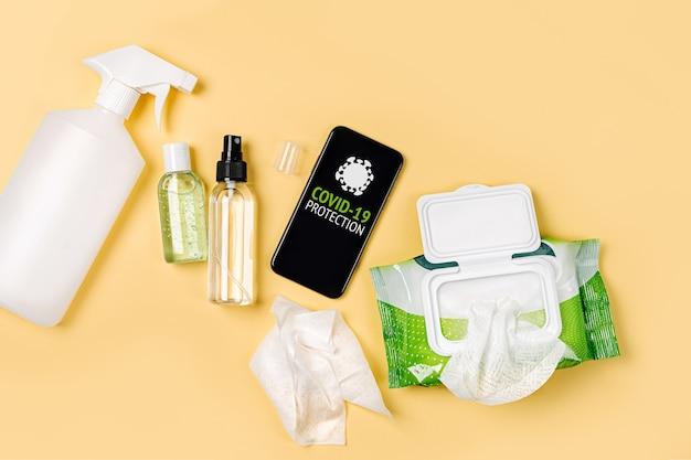 Smartphone mit desinfektionsspray, antibakteriellen feuchttüchern und händedesinfektionsmittel auf gelbem hintergrund. persönliches hygieneprodukt zum schutz vor viren, grippe, coronavirus, covid-19