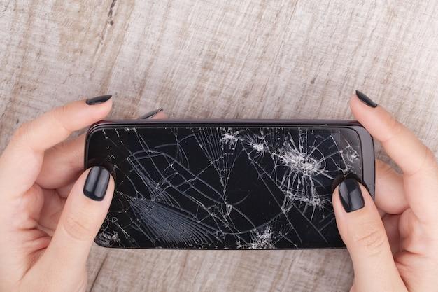 Smartphone mit einem kaputten bildschirm in der hand des mädchens