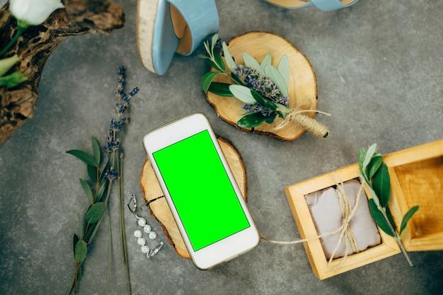 Smartphone mit einem leeren bildschirm liegt auf einem schönen holzständer neben einer schmuckschatulle blumen und
