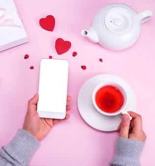 Smartphone mit einem weißen bildschirm in der linken weiblichen hand
