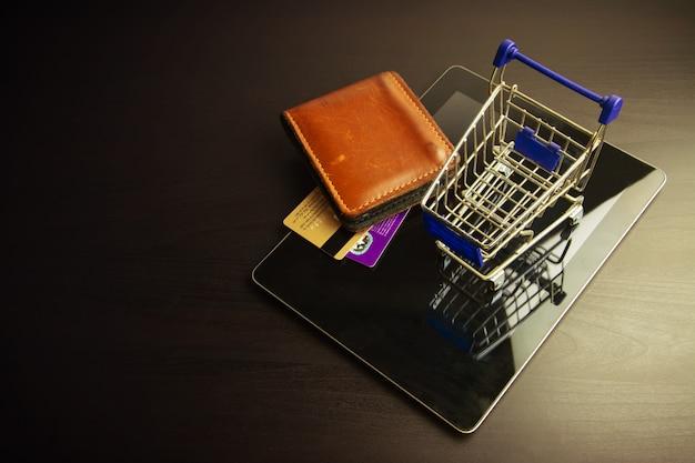 Smartphone mit einkaufswagen auf holz