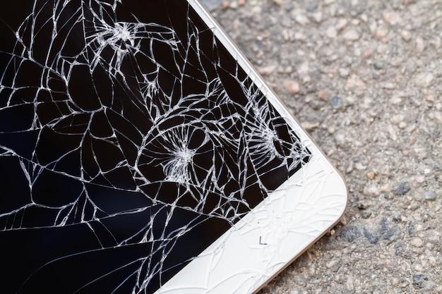 Smartphone mit gebrochenem blauem bildschirm liegt auf dem asphalt.
