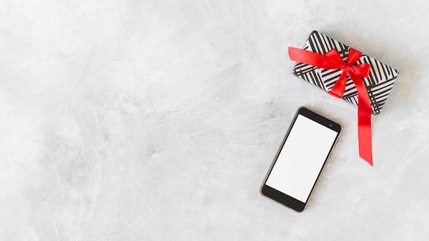 Smartphone mit geschenkbox auf dem tisch
