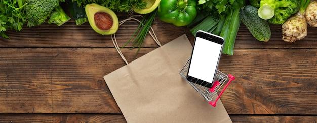 Smartphone mit grünem gemüse auf holztisch mit einkaufswagen. bestellung von lebensmitteln über das mobiltelefon-anwendungskonzept