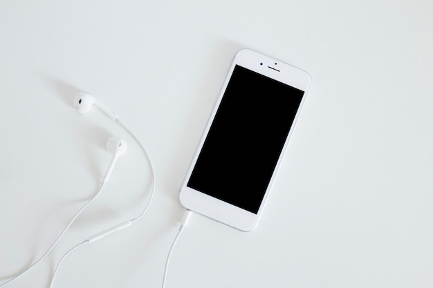 Smartphone mit kopfhörer getrennt auf weißem hintergrund