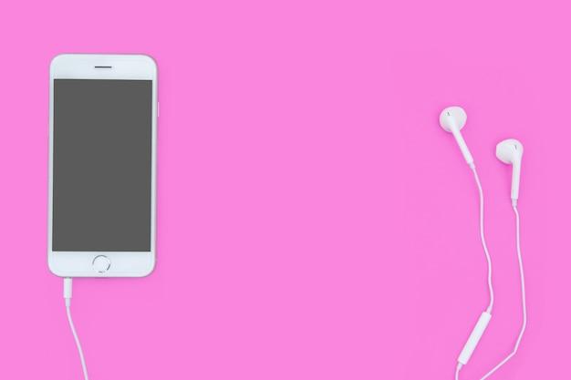 Smartphone mit kopfhörern auf rosa mit kopienraum und beschneidungspfad. flach liegen. ansicht von oben.