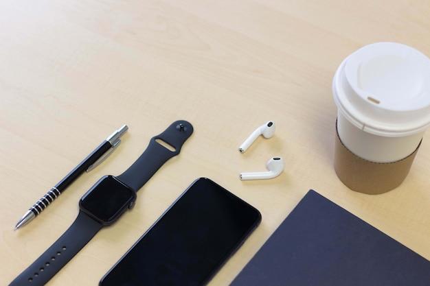 Smartphone mit kopfhörern, wegnehmen pappbecher kaffee und buch auf schreibtisch tisch