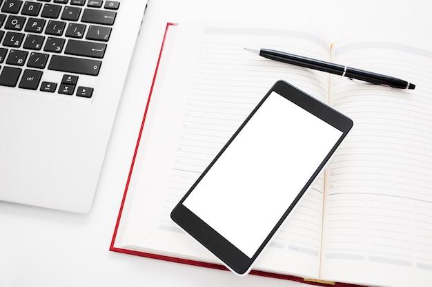 Smartphone mit leerem bildschirm und büromaterial