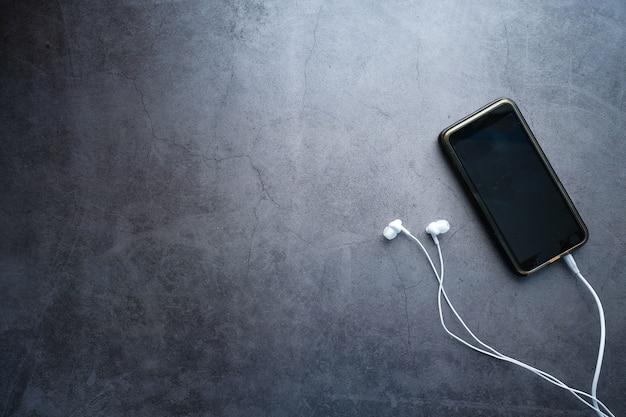 Smartphone mit leerem bildschirm und kopfhörer auf schwarzem hintergrund