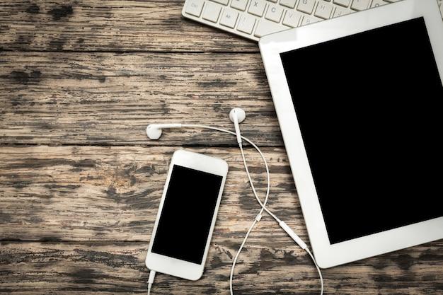 Smartphone mit leerem bildschirm und tisch-pc im hintergrund