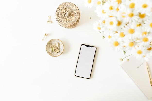 Smartphone mit leerem modellkopierraum auf tisch mit kamille-gänseblümchen-blumenstrauß auf weißer oberfläche