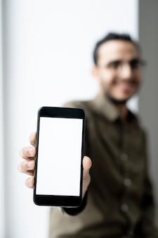 Smartphone mit leerem touchscreen in der hand des jungen zeitgenössischen geschäftsmannes, der vor der kamera steht