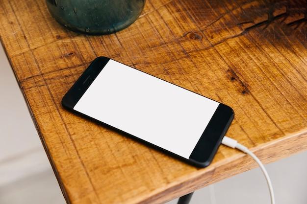Smartphone mit leerem weißem bildschirm auf hölzernem schreibtisch