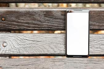 Smartphone mit leerer weißer Bildschirmanzeige auf hölzerner Planke
