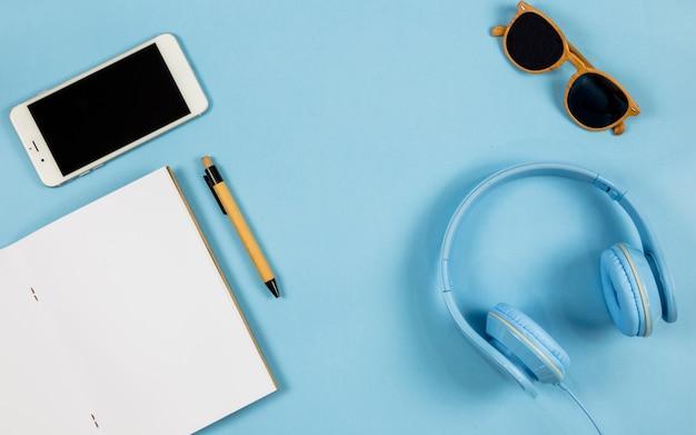 Smartphone mit notizbuch und kopfhörer auf tabelle
